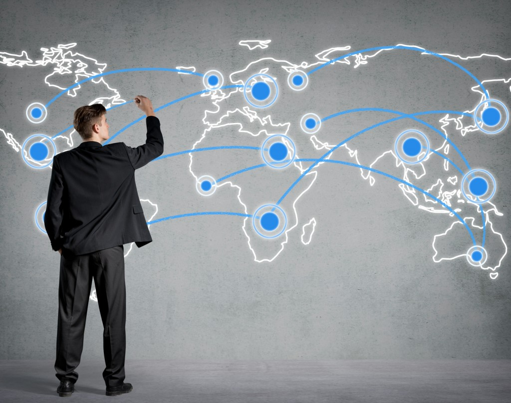Businessman connecting the dots on a world map